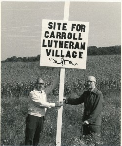 In a photo taken prior to May 1980, Rev. Dr. Harry Krug (left) and Rev. Dr. Elwood Falkenstein (right) hold a sign on the Griswald property along Bell Road in Wakefield Valley, the 40-acre site selected for the future Carroll Lutheran Village.