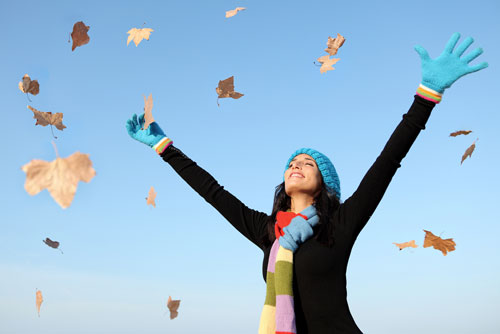 A woman showing gratitude for nature as she is standing with her hands in the air, after throwing leaves in the air with a smile on her face.