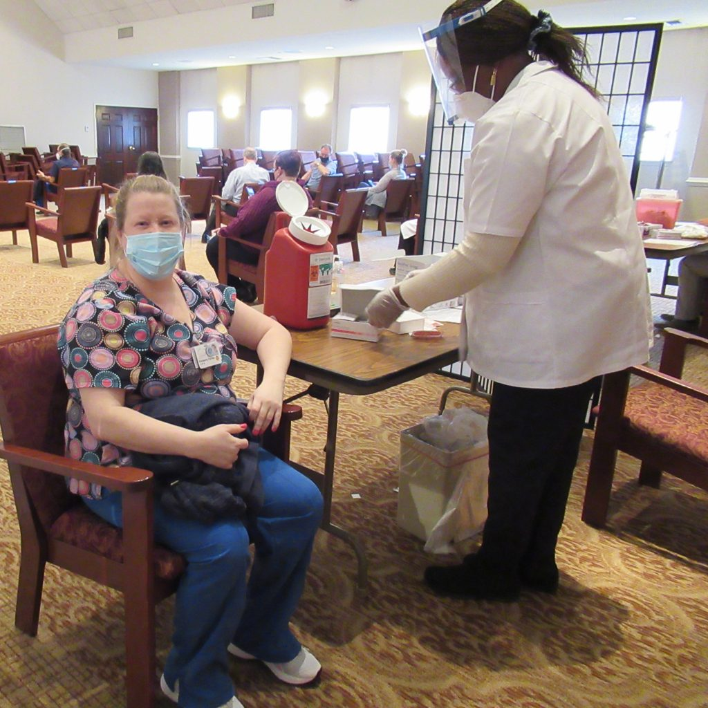 Geriatric Nursing Assistant, Kimberly Farney, sitting in a chair as the vaccination tech prepares to give her the COVID-19 vaccine.