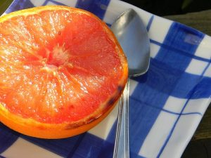 A broiled grapefruit on a plaid plate