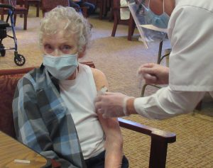 CLV resident, Lois Cook, getting vaccinated from a Walgreens clinical worker.