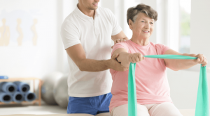 An occupational therapist assisting a female older adult with using a resistance band to improve arm strength.