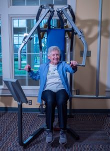 Senior adult woman exercising at the chest press machine.