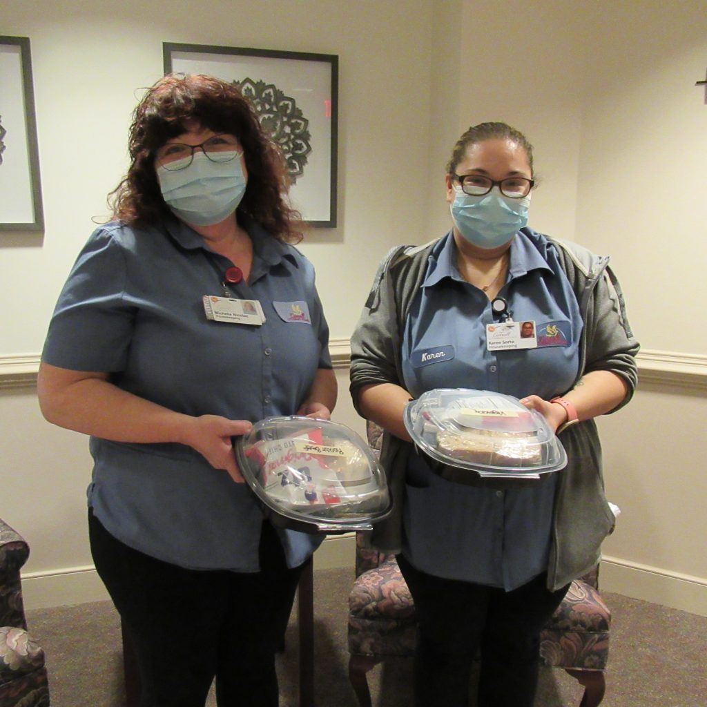 Two team housekeeping team members holding their lunch from Raphael's.