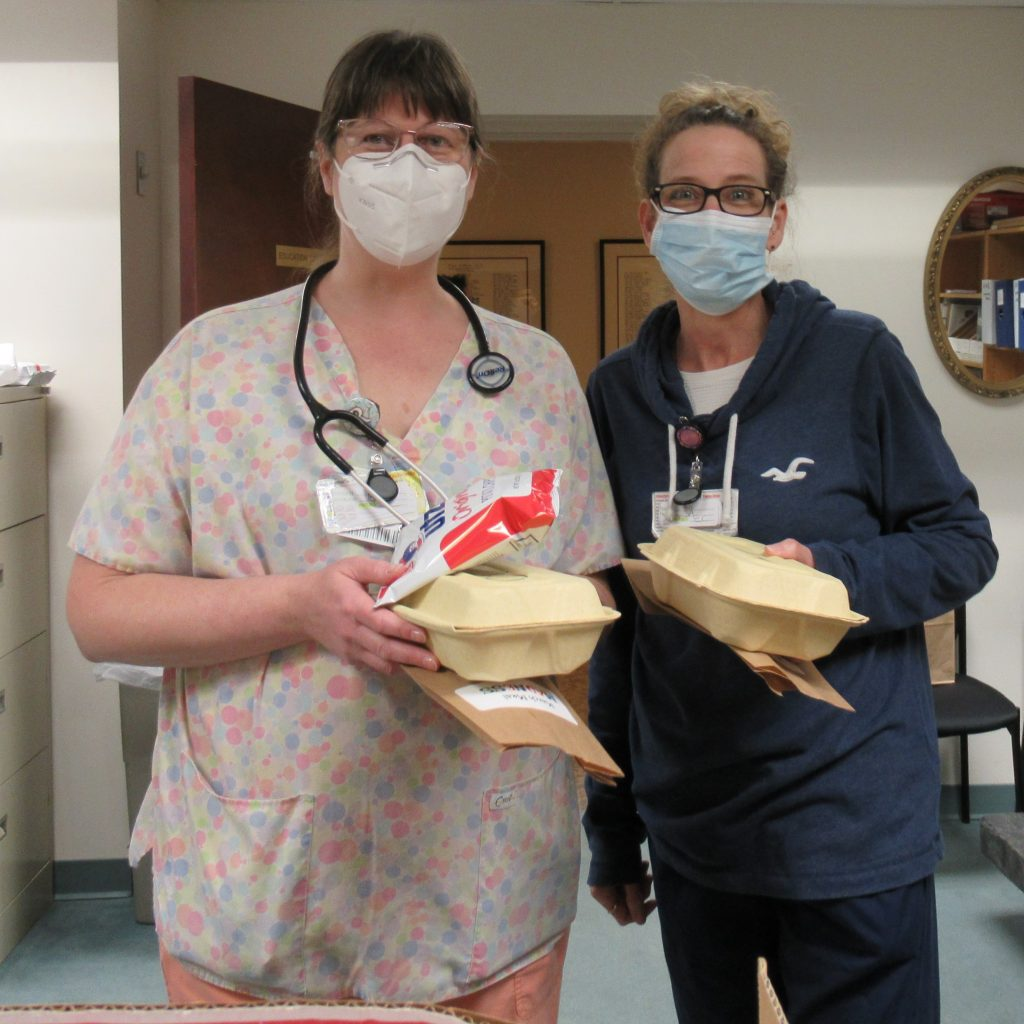 Two female health care workers holding their lunch from Classico Pizzeria.