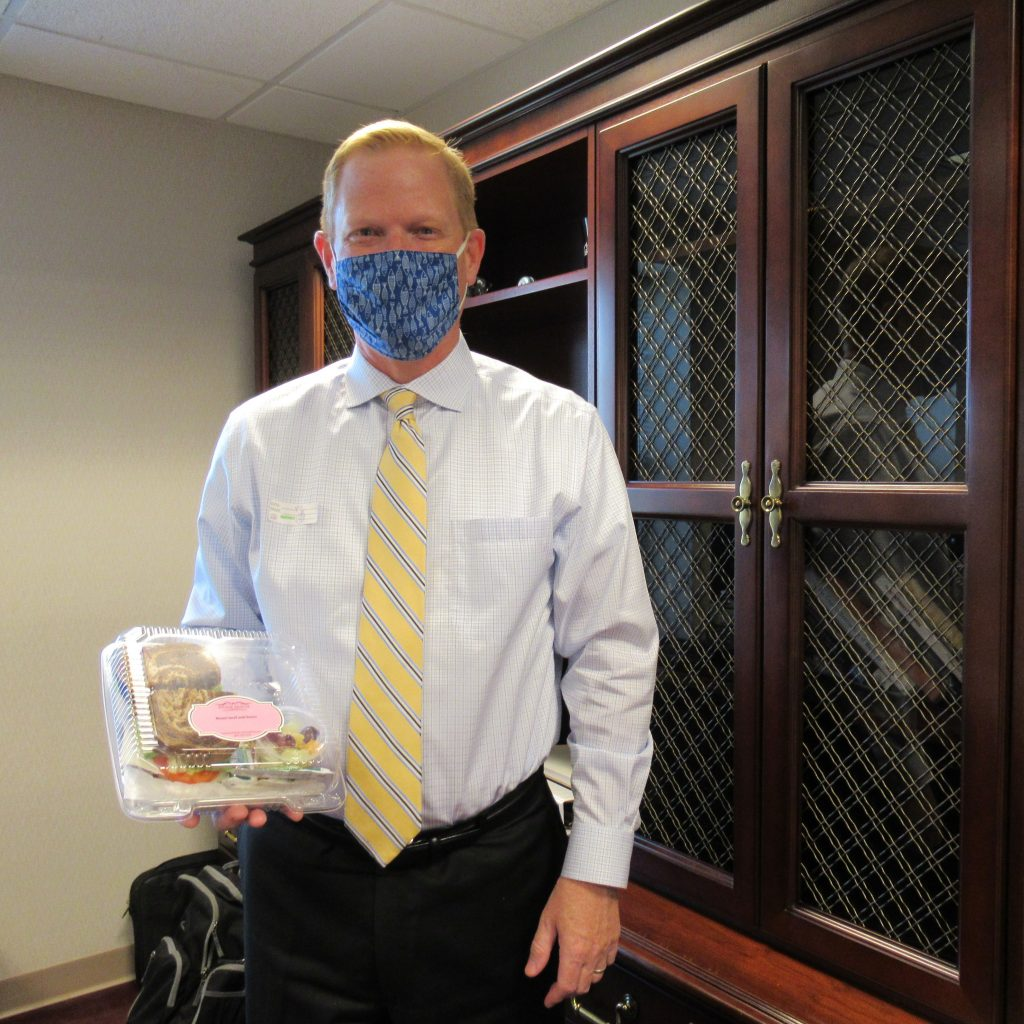 Jeff Branch, president and CEO, holding his lunch from Stonehouse Cakery & Cafe.
