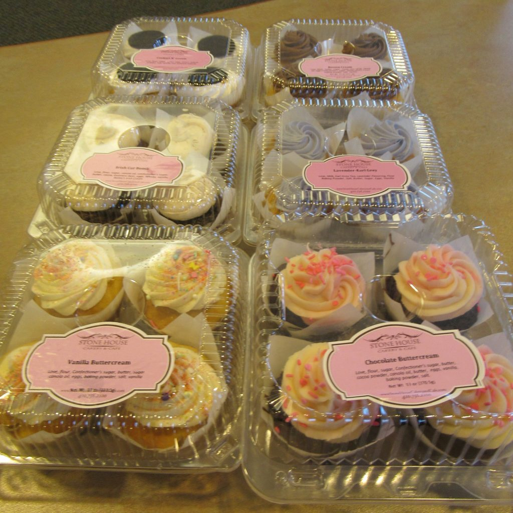 Six containers of Stonehouse Cakery & Cafe cupcakes in assorted flavors.