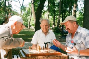 Three men participating in playing a game of chess.