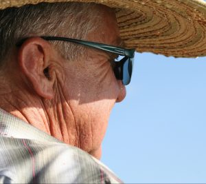 An older man wearing sunglasses and a sun hat