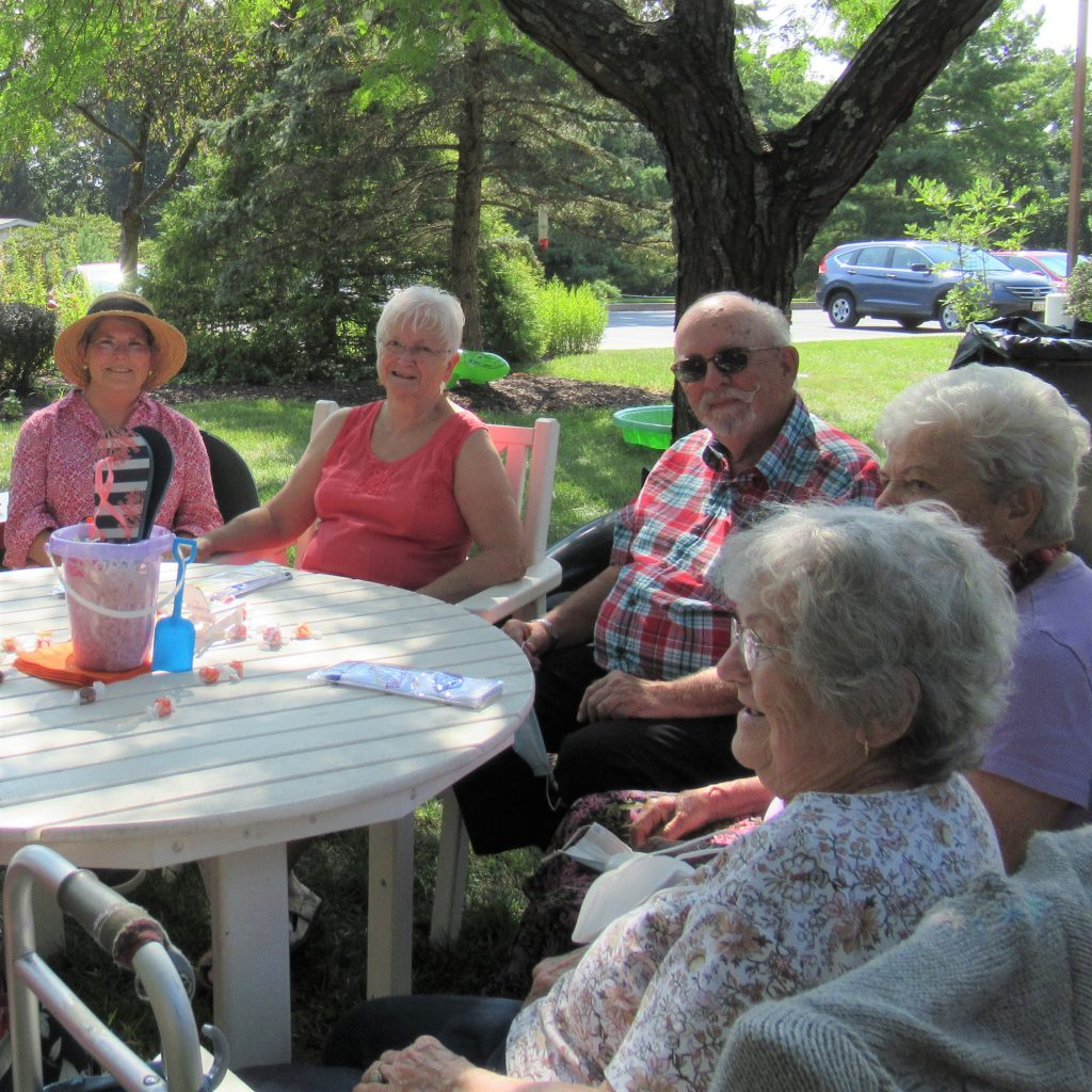 Residents sitting around a table enjoy one another's company.