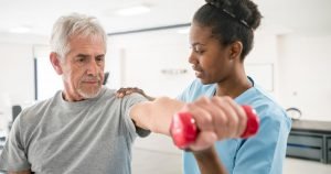 A physical therapist helping a senior man to do a lateral arm raise with a dumbell.