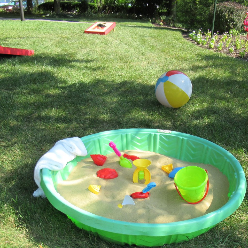 A kiddie pool filled with sand and beach toys with a beach ball and corn hole set in the background.
